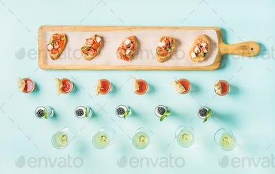 Snacks, brushettas, gazpacho shots, desserts, champagne over pastel blue background