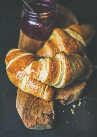 Freshly baked croissants with raspberry jam in jar