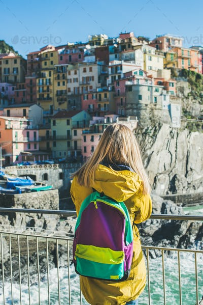 Young blond tourist woman looking at Riomaggiore, Cinque Terre, Italy