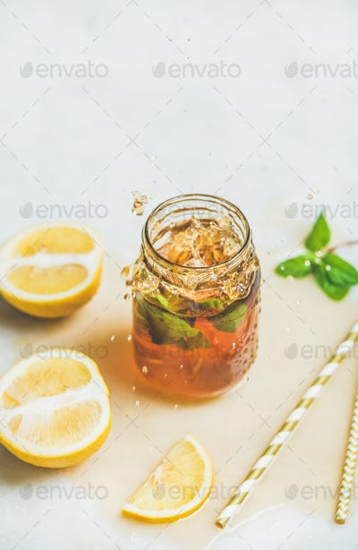 Summer cold Iced tea with lemon and herbs, copy space