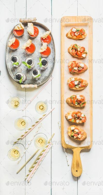 Brushettas, gazpacho shots, desserts, champagne and straws over white background