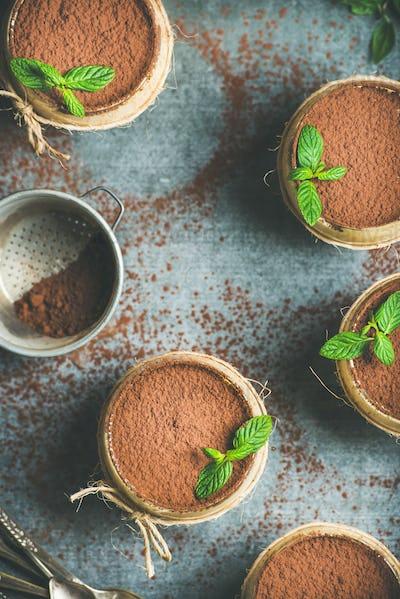 Homemade Italian dessert Tiramisu in glasses with mint, copy space