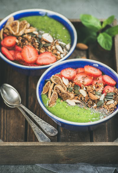 Healthy breakfast, green smoothie bowls with granola, fruit, seeds