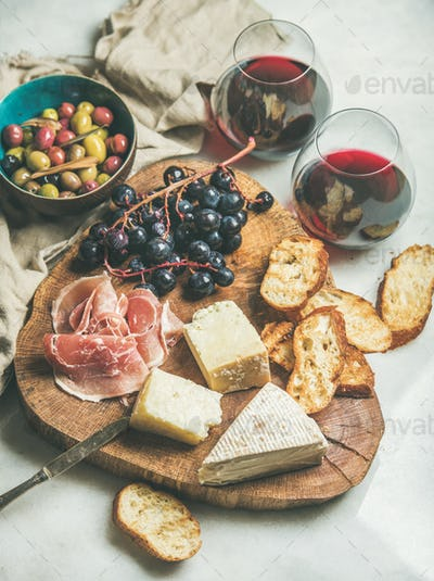 Cheese, olives, prosciutto, baguette slices, grapes and red wine