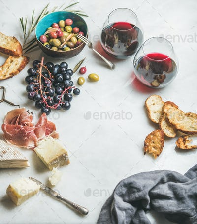 Cheese, olives, grapes, prosciutto, baguette and red wine, copy space