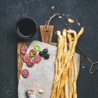 Grissini bread sticks, sausage, olives and red wine, copy space