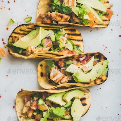 Healthy corn tortillas with grilled chicken fillet, avocado, fresh salsa
