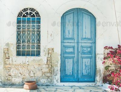 Exterior of Greek island traditional street with blue door, Kast