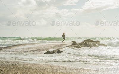 Young woman standing on pier and looking at stormy sea