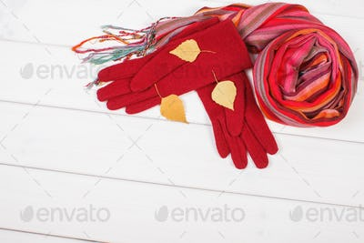 Gloves and shawl for woman on white boards, clothing for autumn or winter, copy space for text