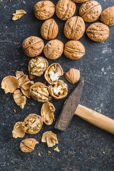 Tasty dried walnuts and hammer.