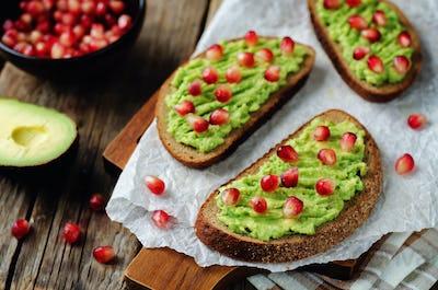 Smashed avocado pomegranate rye sandwiches