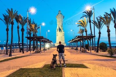 Wanderlust man and dog at Cristofer Collumbus monument in Spain