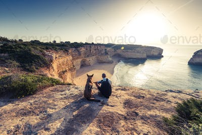 Best friends travellers sitting at cliffs in Portugal