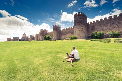 Man laying on grass with dog by city Avila,Spain