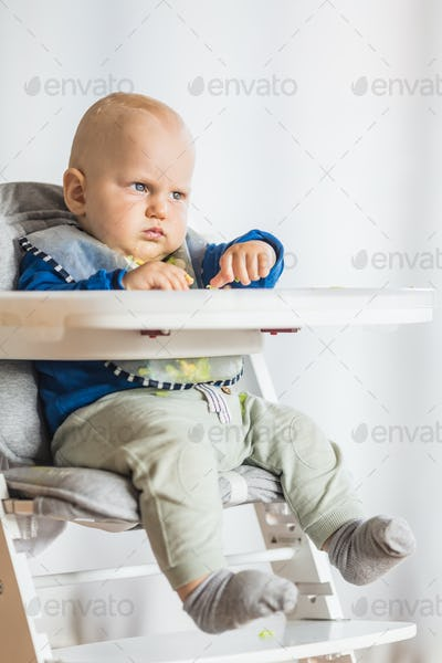 Baby boy serious eating with BLW method, baby led weaning