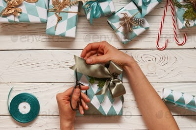 Woman wrapping christmas presents over wooden background