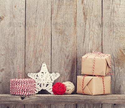 Christmas gift boxes and decor in front of wooden wall