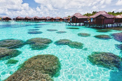 Over water bungalows and lagoon with coral