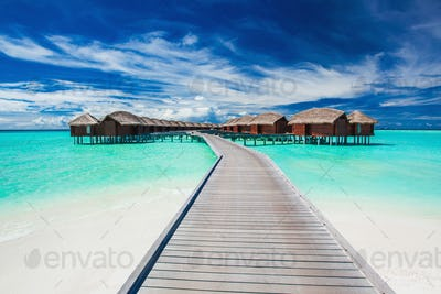 Overwater villas on the tropical lagoon connected by jetty