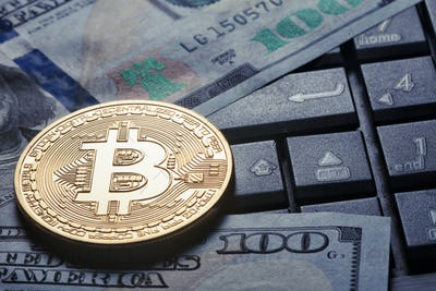 Virtual currency bitcoin against the background of dollars and c
