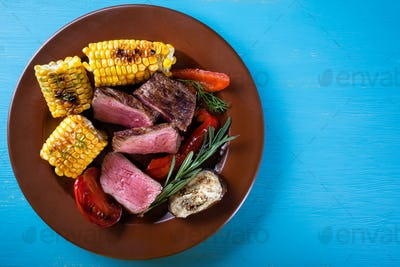 Slices of fried meat with corn and vegetables on plate
