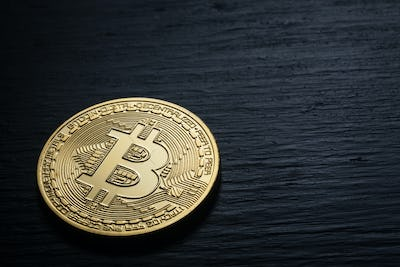 Golden shiny bitcoin on a black wooden background