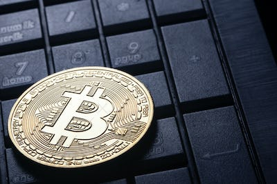 Virtual currency is the golden bitcoin on the computer keyboard