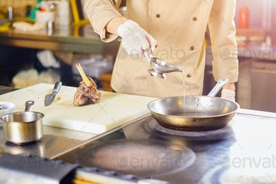 Chef pouring cooking oil into frying pan