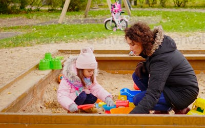 Mother playing with her daughter in a sandbox