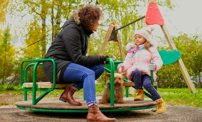 Mother with daughter riding carousel