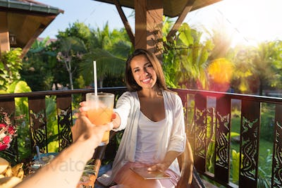 Cheerful Woman Toasting Glass With Juice With Man Sitting On Summer Terrace Pov Of Couple Having
