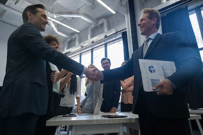 Business Handshake With Businesspeople On Background, Colleagues Shaking Hands During Meeting After