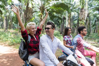 Happy Free Couples Driving Scooter Enjoy Travel In Tropical Forest Cheerful Friends Road Trip