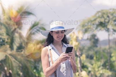 Attractive Woman In Hat Communicating With Cell Smart Phone Over Tropical Forest View Young Girl