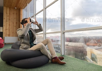 Business Man Wear Digital Glasses Hold Hand Virtual Reality Sit in front Panoramic Window