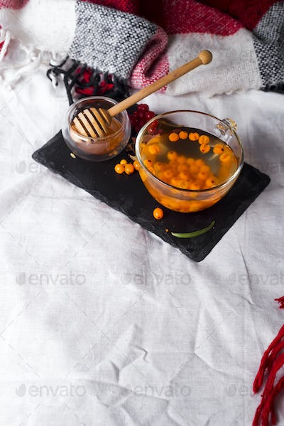 tray with honey and a cup of hot tea in the bed,