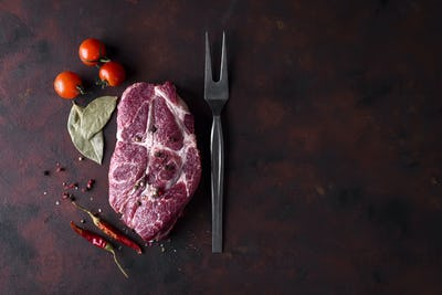 Raw steak with spices and ingredients for cooking.