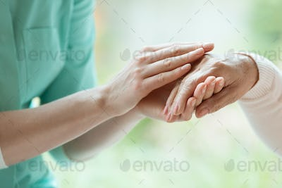 Caretaker massaging pensioner's hand