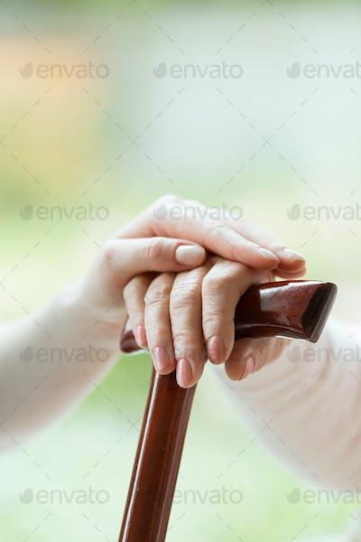 Caregiver's hand on elder's hand