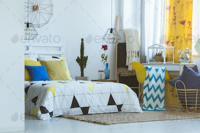 Trendy bedroom with yellow accessories