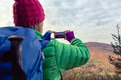 Hiking woman with backpack taking photo with smartphone
