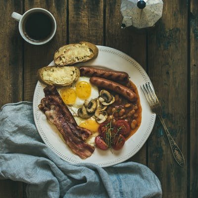 Traditional English breakfast with fried eggs, sausages, mushrooms, bacon, coffee