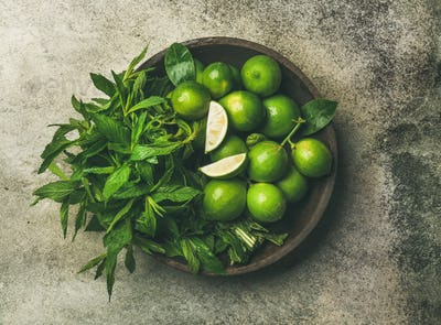 Flatlay of fresh limes and mint in wooden plate