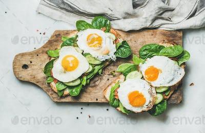 Healthy breakfast sandwiches on rustic wooden board, top view