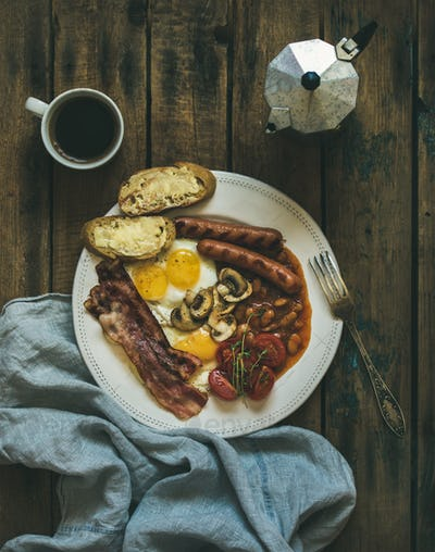 Traditional English breakfast with fried eggs, sausages, mushrooms, bacon