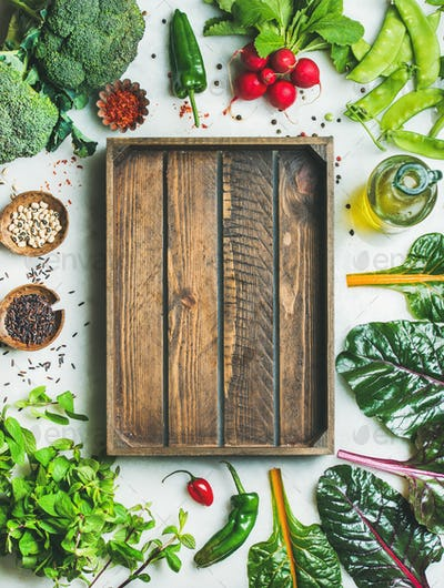 Fresh greens, vegetables and grains with wooden box in center