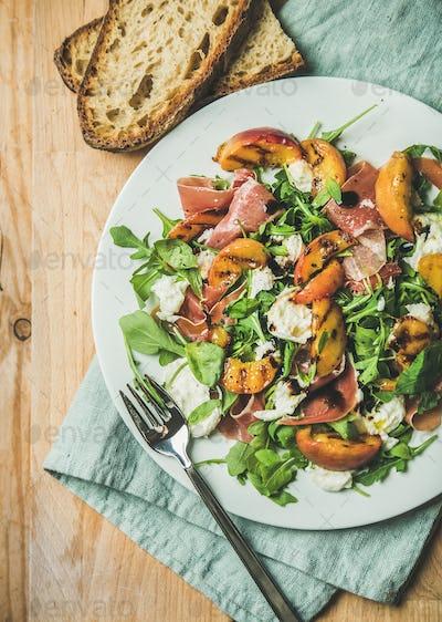 Arugula, prosciutto, mozzarella and grilled peach salad in white plate