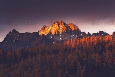 Last sun light hits high mountains peak at sunset