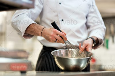 Chef in hotel or restaurant kitchen cooking, only hands. He is whisking ingredients.